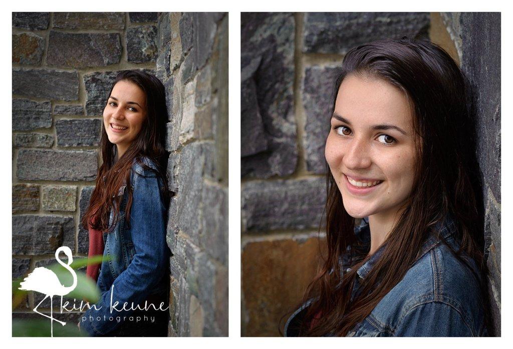 high school senior posing against a stone wall wearing a denim jacket