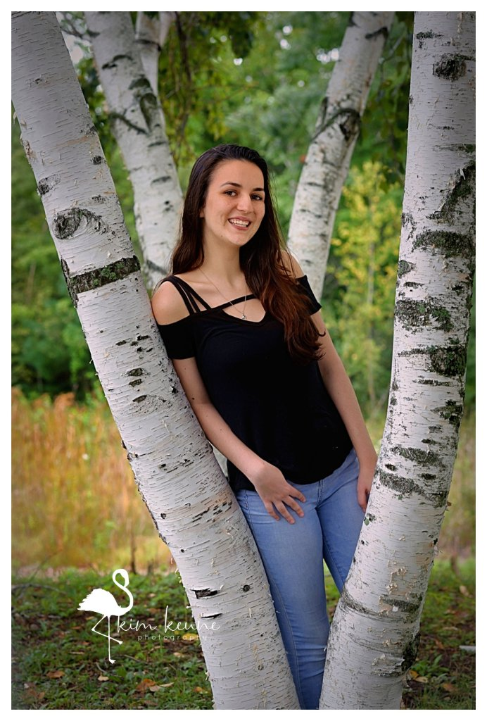 teenage girl nestled between two birch trees in Lincoln Woods State Park RI